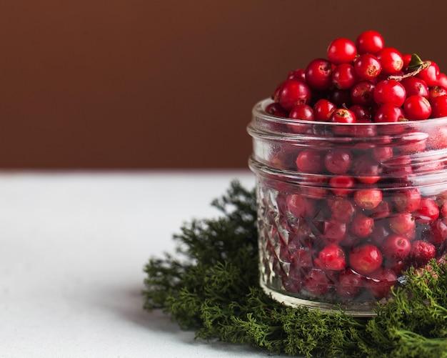 Canneberges fraîches mûres dans un bocal en verre transparent sur la mousse. la tendance des photos culinaires. baies d'automne