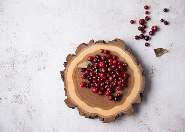 Canneberges fraîches sur une souche en bois sur un fond clair. vue de dessus et espace de copie