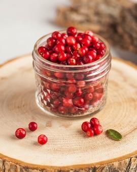 Canneberges mûres fraîches dans un bocal en verre transparent sur un support en bois. l'automne, baies utiles. récolte..