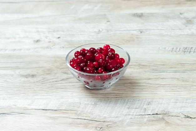 Canneberges rouges dans un bol en verre sur un fond en bois blanc