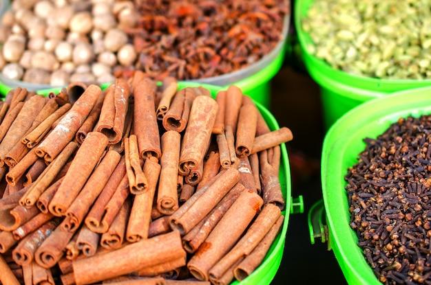 Cannelle et autres épices sur le marché dans des récipients colorés.
