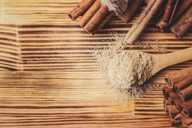 Cannelle moulue et des bâtons sur un fond en bois. mise au point sélective.