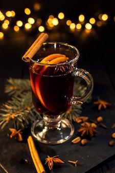 La cannelle se trouve dans un verre, un verre de vin chaud en gros plan avec de l'orange et de la cannelle sur fond noir foncé, un arbre de noël et des lumières, un grand bokeh jaune, un ensemble de vin chaud