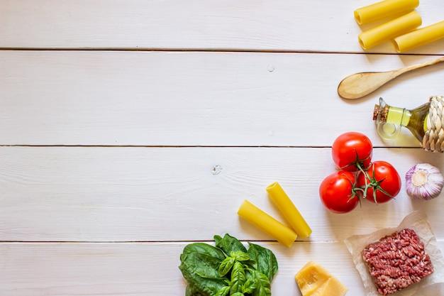 Cannellonis, tomates, viande hachée et autres ingrédients. fond en bois blanc cuisine italienne.