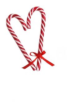 Cannes de bonbon formant un coeur avec un petit ruban sur un et isolé sur blanc