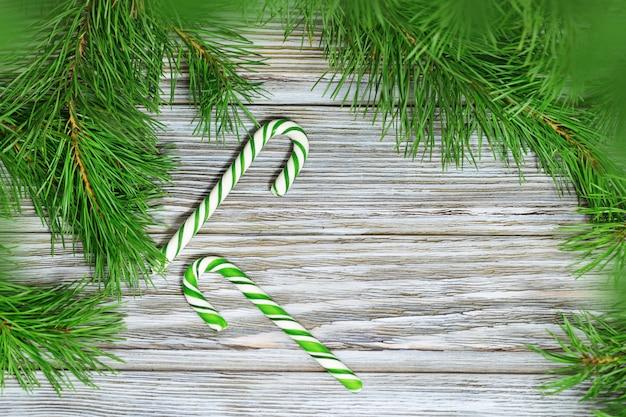 Cannes de bonbon vert et branches de pin sur fond en bois