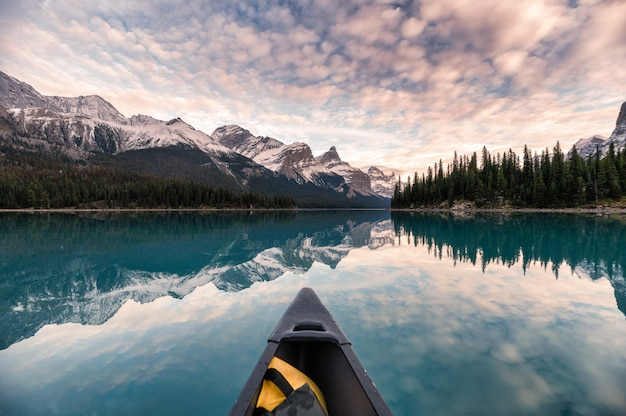 Canoë sur le lac maligne avec réflexion des rocheuses canadiennes dans spirit island au parc national jasper