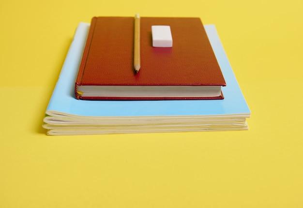 Un caoutchouc, un crayon sur un livre à couverture rigide, des manuels, isolés sur fond jaune avec espace de copie