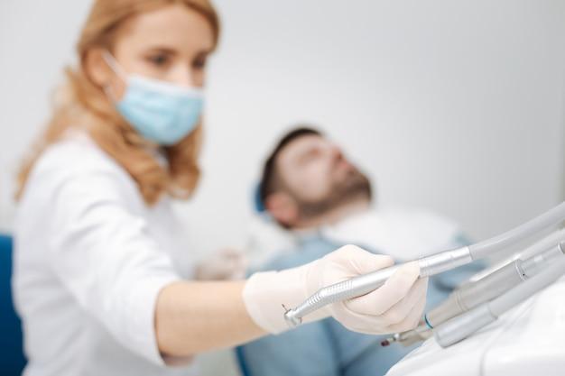 Capable forte femme brillante prenant un foret dentaire pour traiter ses patients caries en remplissant l'une de ses dents