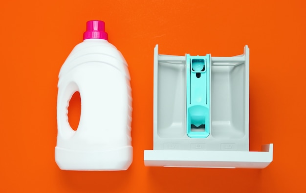 Capacité de la machine à laver pour la poudre, bouteille de gel de lavage sur fond orange. vue de dessus, pose à plat