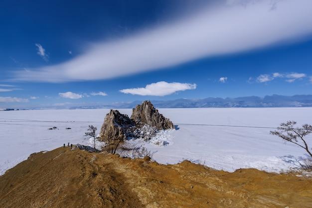 Cape burhan sur shamanka rock dans l'île d'olkhon en journée ensoleillée de mars. lac baïkal avec de beaux nuages