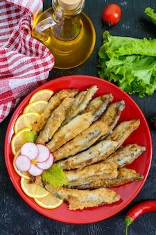Capelan frit au citron sur une plaque rouge sur un fond en bois noir. un plat de petits poissons de mer. vue de dessus. mise à plat