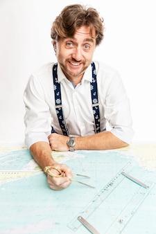 Un capitaine souriant mignon mesure la distance sur une carte avec une boussole. mur blanc. verticale.