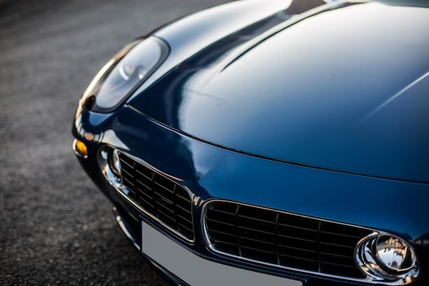 Capot avant et phare d'une voiture noire