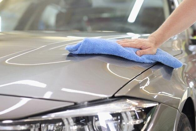 Le capot de la voiture grise est essuyé avec de la microfibre au concept de soins de voiture de lavage de voiture