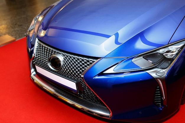 Capot de voiture de sport bleu incurvé montrant une réflexion abstraite.