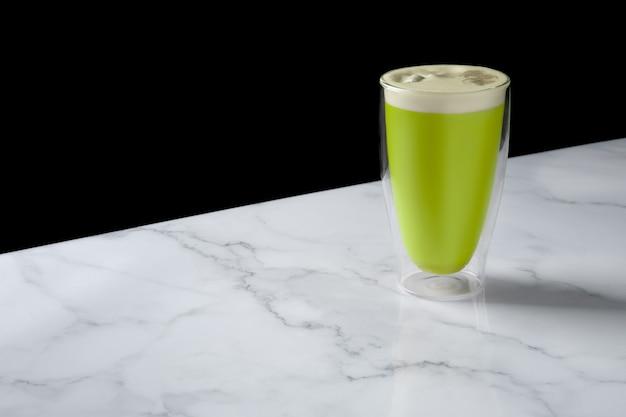 Cappuccino au thé matcha en verre à double paroi.