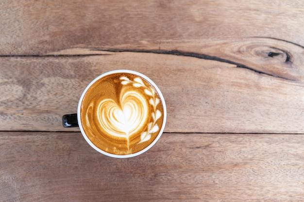 Cappuccino de café d'art chaud dans une tasse sur fond de table en bois avec espace de copie
