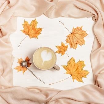 Cappuccino café avec coeur d'art et feuilles automnales jaunes sur fond de bois blanc