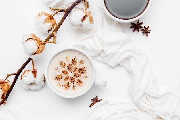 Cappuccino de café avec des étoiles de cannelle et d'anis sur fond blanc.