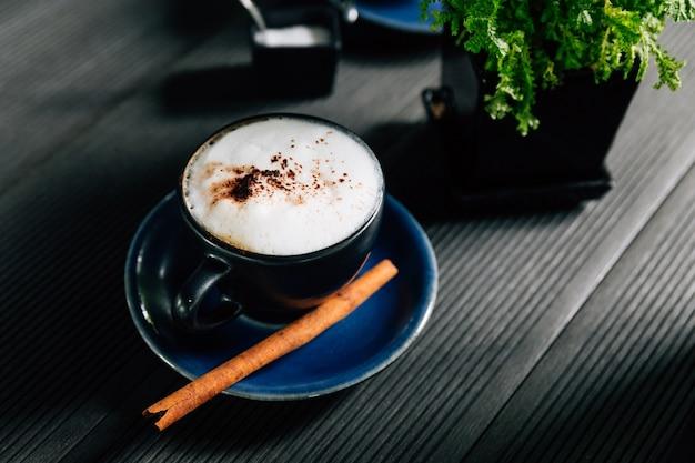Cappuccino chaud à la cannelle servi dans une tasse bleue.