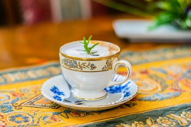 Cappuccino chaud dans une tasse en céramique blanche sur la nappe de luxe et une table en bois, vue latérale