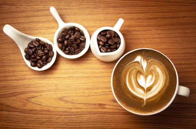 Cappuccino chaud avec des grains de café torréfiés sur une surface en bois