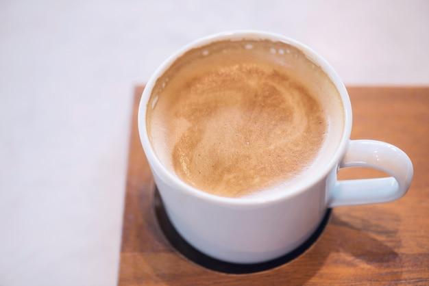 Cappuccino chaud avec de la mousse de lait mousseuse dans une tasse de café blanc sur une plaque en bois par vue de dessus