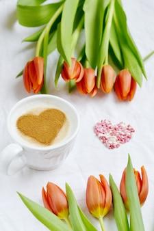 Cappuccino avec coeur de cannelle et fleurs composition tulipes, valentin concept de printemps
