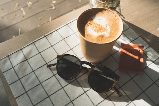 Cappuccino dans une tasse de café à emporter sur une nappe avec des fleurs séchées, lunettes de soleil sur la table