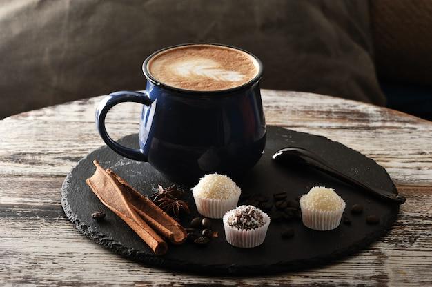 Cappuccino dans une tasse, cannelle et petits gâteaux à la crème et au chocolat