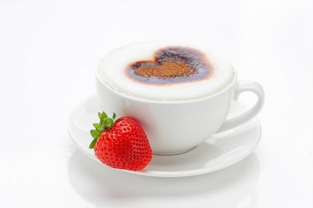 Cappuccino dans une tasse en forme de coeurs et fraises isolés on white