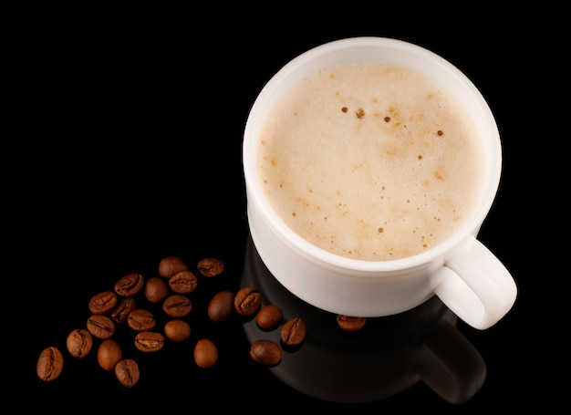 Cappuccino dans une tasse avec mousse et grains de café fond noir