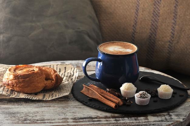 Cappuccino dans une tasse, pâte à la cannelle, petits gâteaux et cannelle