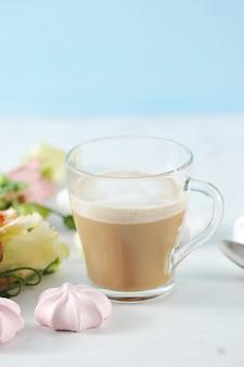 Cappuccino dans une tasse transparente avec des fleurs et guimauve