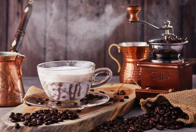 Le cappuccino est une boisson au café à base d'expresso et de mousse de lait cuit à la vapeur à base de café dans une tasse en verre transparent. café chaud avec de la vapeur, des grains de café et un moulin à café manuel