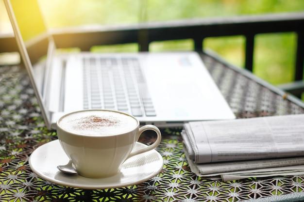 Cappuccino avec journal, ordinateur portable ou ordinateur portable sur la table vintage du matin