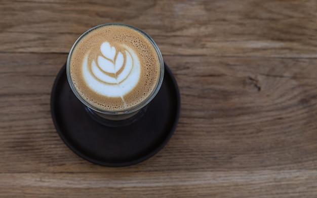 Cappuccino avec latte art dans une tasse en verre sur une table en bois dans un café ou un café
