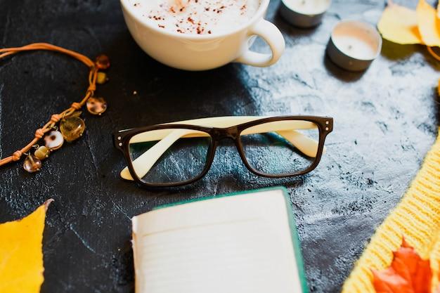 Un cappuccino, des lunettes et un pull jaune vif s'allongent sur l'obscurité