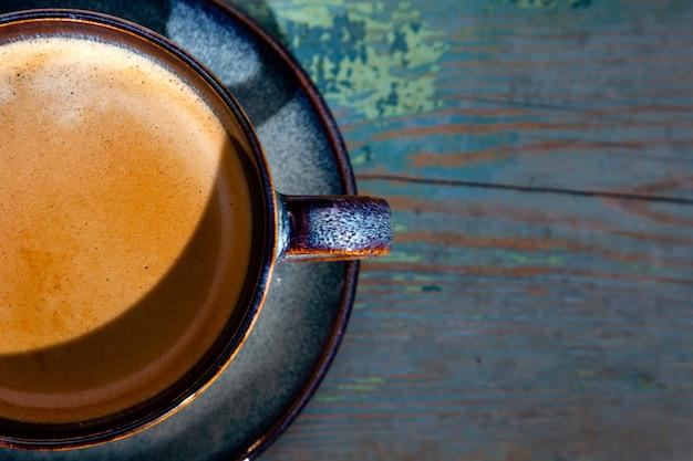 Cappuccino avec mousse, tasse à café bleue sur fond de bois