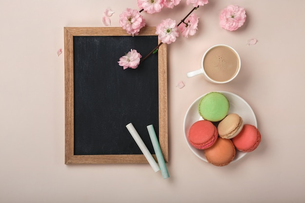 Cappuccino tasse blanche avec des fleurs de sakura, macarons, tableau à craie sur un fond rose pastel