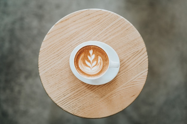 Cappuccino sur une tasse en céramique blanche avec une soucoupe sur la table ronde brune