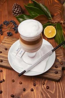 Cappuchino mousse au chocolat et à la vanille, lait frappé dans une tasse en verre