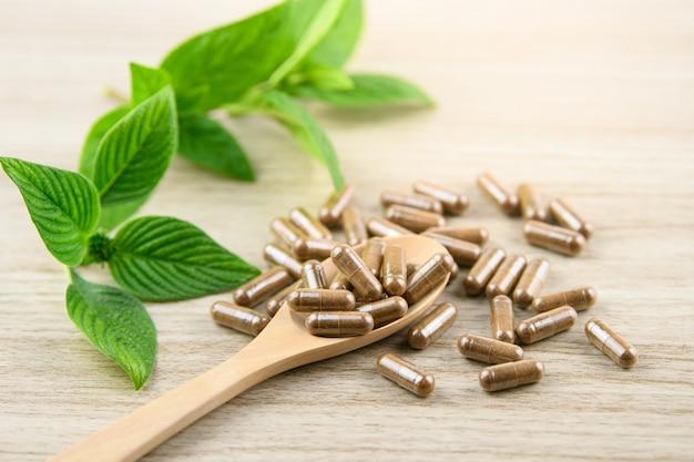 Capsule à base de plantes provenant d'herbes naturelles pour une bonne santé, pilules supplémentaires sur une table en bois