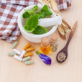 Capsule à base de plantes de soins de santé alternative avec du mortier sur fond en bois.