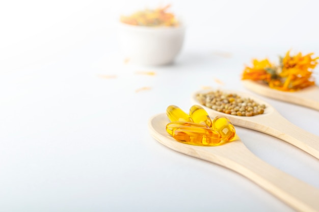 Capsule à base de plantes, vitamines naturelles, fleurs de calendula sec à la cuillère en bois sur fond blanc. concept de soins de santé et de médecine alternative: homéopathie et naturopathie.