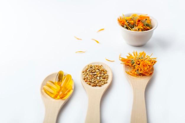 Capsule à base de plantes, vitamines naturelles, fleurs de calendula sec à la cuillère en bois sur fond blanc. concept de soins de santé et de médecine alternative