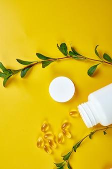 Capsule biologique à base de plantes de médecine alternative avec vitamine e, huile de poisson oméga trois avec des feuilles vertes, concept de soins de santé, alimentation saine