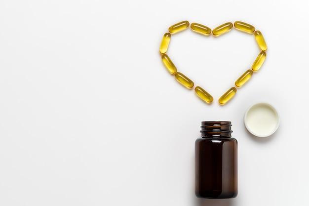 La capsule d'huile de poisson est disposée en forme de cœur sur un fond blanc.