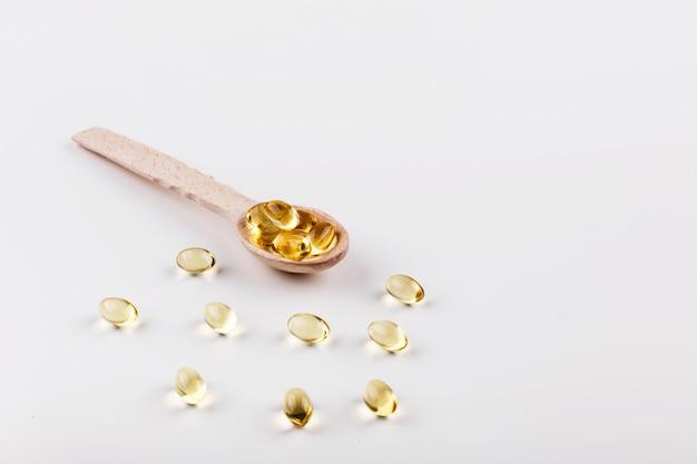 Capsule d'huile pour les cheveux avec de la vitamine e se trouvent sur une cuillère en bois